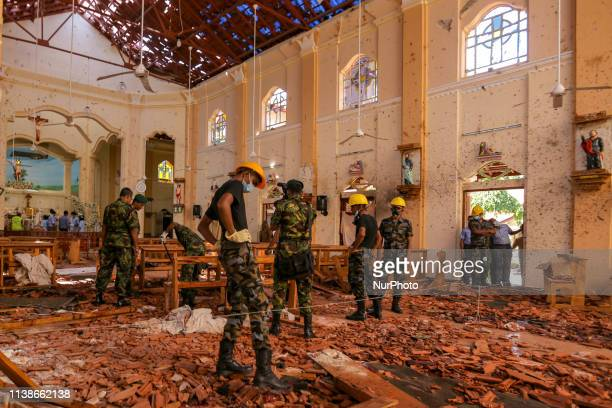 Sri Lankan military officers conduct inspections inside the St. Sebastians church where a bomb blast took place in the town of Negombo, 30kms off...