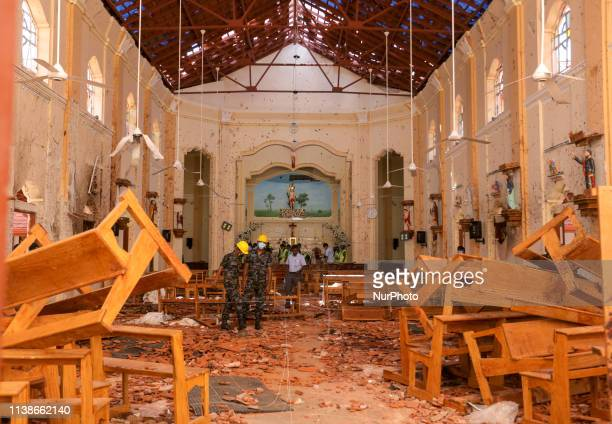 Sri Lankan military officers conduct inspections inside the St Sebastians church where a bomb blast took place in the town of Negombo 30kms off...