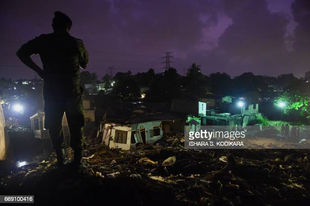 A Sri Lankan military official stands overlooking damaged homes at the site of a collapsed garbage dump in Colombo on April 16 2017 Hopes of finding...