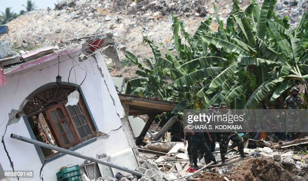 Sri Lankan military officials stand among damaged homes at the site of a collapsed garbage dump in Colombo on April 18 2017 Hundreds of tonnes of...