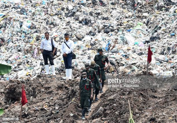 TOPSHOT Sri Lankan military officials walk among garbage and damaged homes at the site of a collapsed garbage dump in Colombo on April 18 2017...