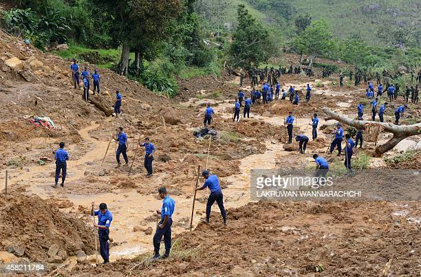 Sri Lankan military personel use poles and hoes during a search operation at the site of a landslide caused by heavy monsoon rains in Koslanda...