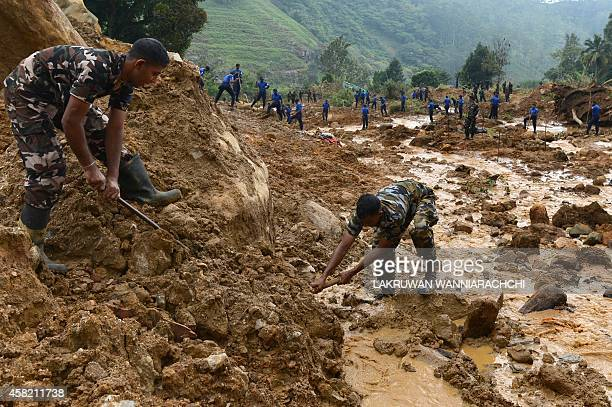 Sri Lankan military personel use poles during a search operation at the site of a landslide caused by heavy monsoon rains in Koslanda village in...