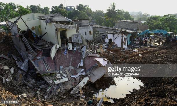 Sri Lankan military personnel use heavy machinery as they search for possible survivors at the site of a collapsed garbage dump in Colombo on April...