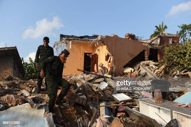 Sri Lankan military personnel walk among damaged homes at the site of a collapsed garbage dump in Colombo on April 16 2017 Hopes of finding anyone...
