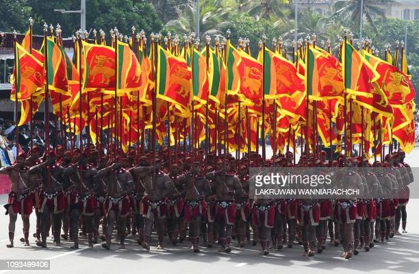 TOPSHOT Sri Lankan military personnel with the army culutural troupe march in traditional dress holding the national flag during the island's 71st...