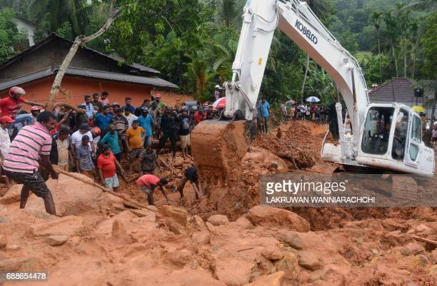 Sri Lankan military rescue workers and villagers search for survivors at the site of a mudslide in Bellana village in Kalutara on May 26 2017...
