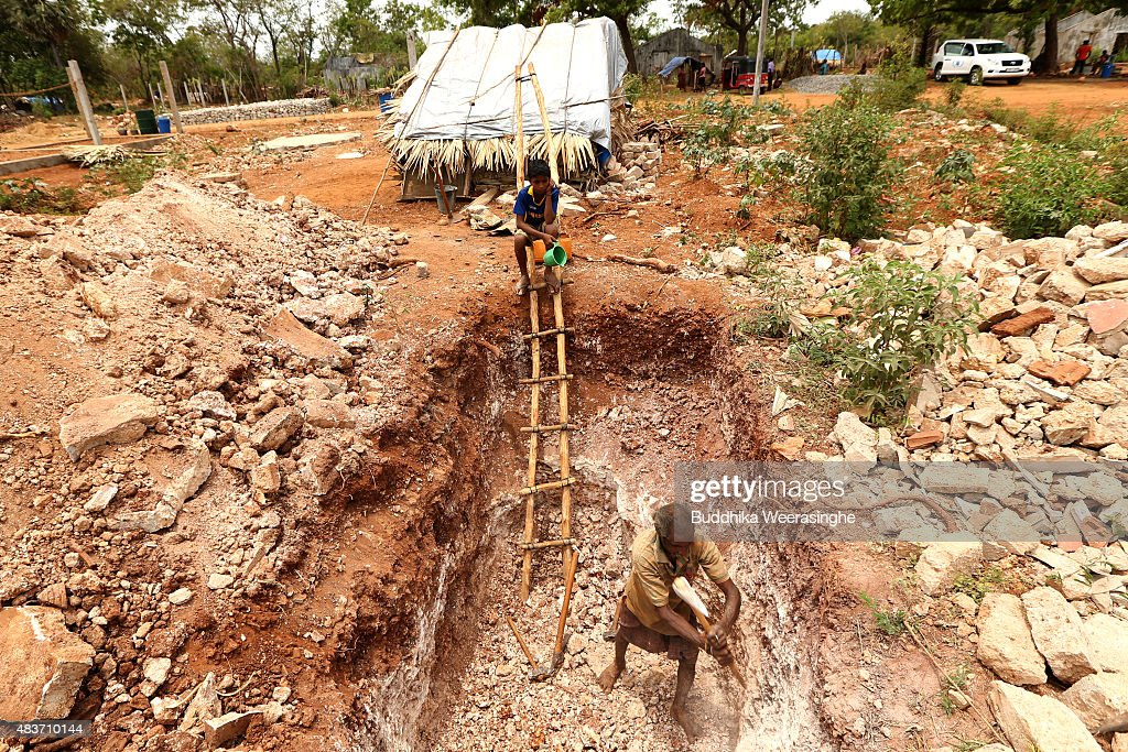 Sri Lankan minority ethnic Tamil man, Nagamuththu Nawarathnam,57, digs a cesspit as his son N Gajatheepan sits on ladder in the land which has been recently released back to owners in April after 25 years as a military forces high security zone in the remote village of Thillipali on August 12,2015 in Jaffna, Sri Lanka. The UN's Human Rights Council investigation into alleged war crimes committed by both the Sri Lankan Government and the Liberation Tigers of Tamil Eelam (LTTE) during the Sri Lankan Civil War is due to be released in September.