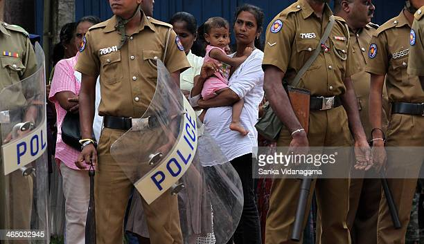 Sri Lankan mother and child look at riot police during pro-government activists demonstration against the alleged contamination of milk powder in...