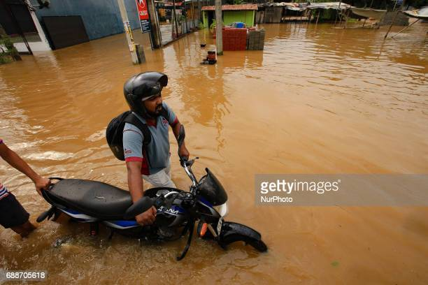 A Sri Lankan motorcyclist pushes his bike across a road inundated by floods at Kaduwela 20kms away from capital city Colombo Sri Lanka Friday 26th...