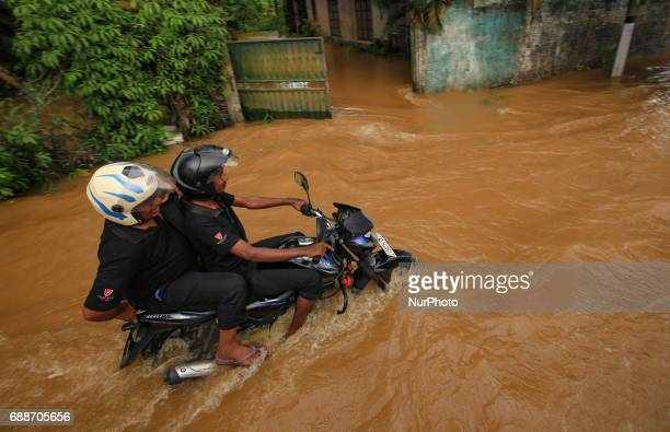 A Sri Lankan motorcyclist rides his bike across a road against the inundated water caused by floods at Kaduwela 20kms away from capital city Colombo...