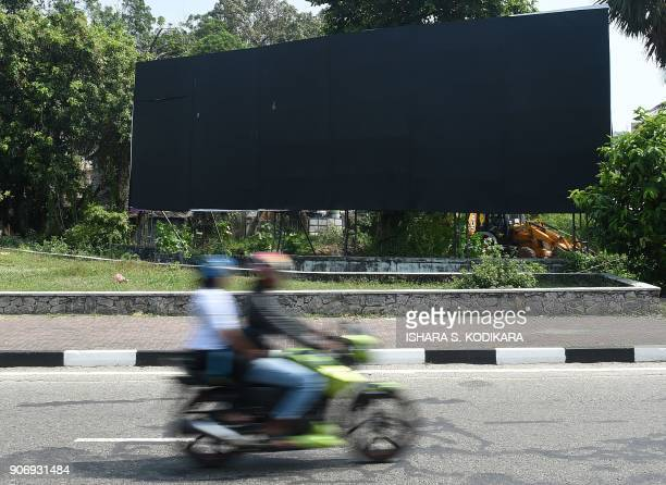 Sri Lankan motorcyclists ride past a blackedout billboard along the Ceremonial Drive to parliament in Colombo on January 19 2018 The billboard...