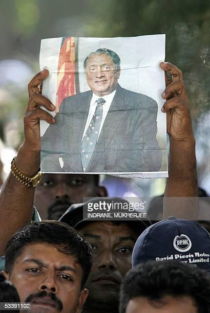 Sri Lankan mourner holds a poster of slain Sri Lankan Foreign Minister Lakshman Kadirgamar during his funeral service in Colombo 15 August 2005...
