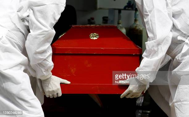 Sri Lankan municipal cemetery workers dressed protective suits and gloves carry a coffin of a Covid-19 virus victim for cremation at Colombo, Sri...