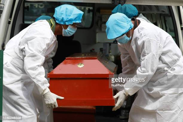 Sri Lankan municipal cemetery workers dressed protective suits carry a coffin of a Covid-19 virus victim for cremation at Colombo, Sri Lanka. 21...