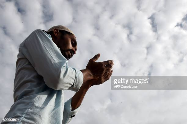 A Sri Lankan Muslim man offers Eid alFitr prayers at the Galle Face esplanade in Colombo on June 26 2017 Muslims around the world are celebrating Eid...