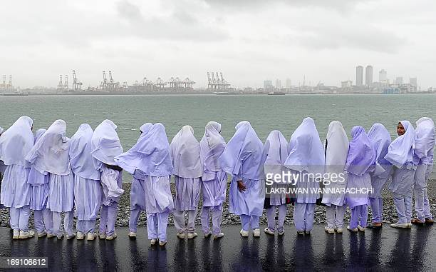 Sri Lankan Muslim school girls stand on the edge of a sea port in Colombo on May 20 after travelling from their town of Kalmunai over 370 kilometres...