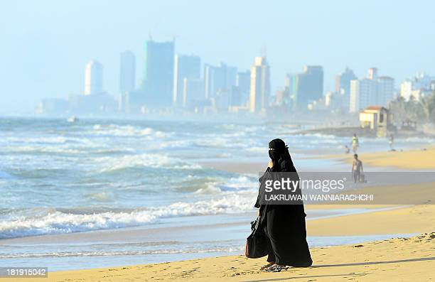A Sri Lankan Muslim woman walks on the beach in Colombo on September 26 2013 Sri Lanka's youth population aged 10 to 19 make up some 15 percent of...