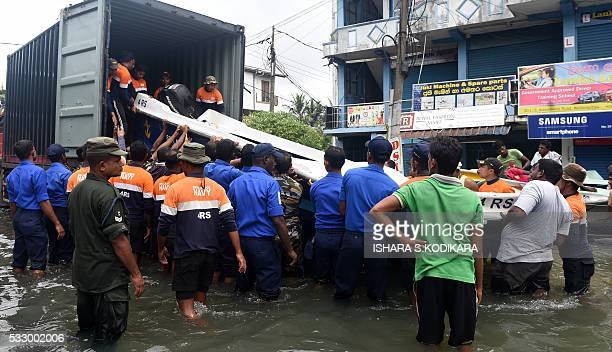 Sri Lankan navy and army personnel evacuate residents following flooding in the Kolonnawa suburb of Colombo on May 20 2016 Desperate Sri Lankans...