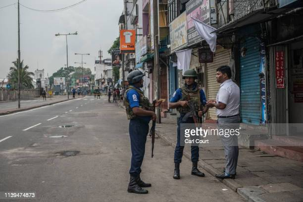 Sri Lankan Navy personnel check a man's identity card on a street near the port on April 26 2019 in Colombo Sri Lanka The Sri Lankan Health Ministry...