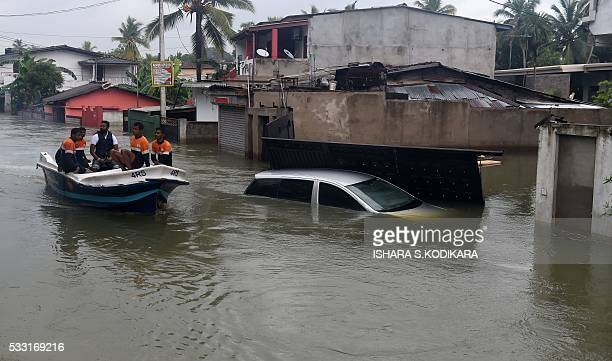 Sri Lankan navy personnel evacuate residents following flooding in the Kolonnawa suburb of Colombo on May 21 2016 Foreign aid began arriving in Sri...