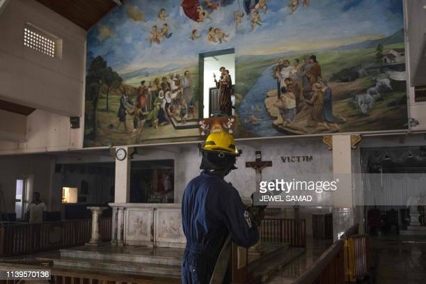 Sri Lankan Navy soldier holds a water hosepipe as he works to clean St. Anthony's Shrine in Colombo on April 27 following a series of bomb blasts...