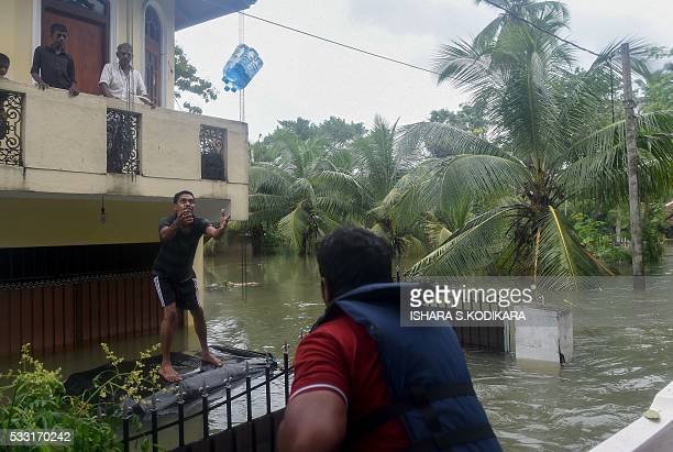 A Sri Lankan navy soldier throws bottles of drinking water to a flood victim in the Kolonnawa suburb of Colombo on May 21 2016 Foreign aid began...
