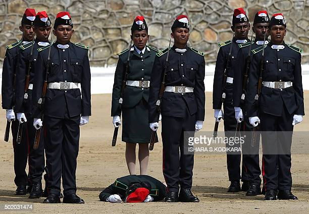 TOPSHOT Sri Lankan officer cadets stand to attention for the national anthem as one of their women colleagues lays down after fainting during a...