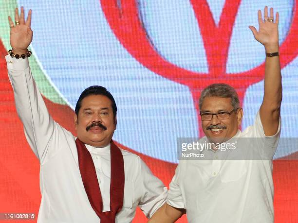 Sri Lankan opposition leader and former president Mahinda Rajapaksa acknowledges supporters with his brother, Sri Lanka's newly elected presidential...