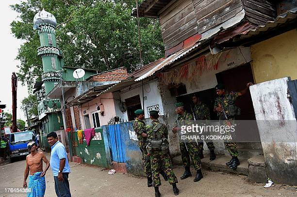 Sri Lankan paramilitary Special Task Force commandos stand guard outside the premises of a vandalized mosque in the capital Colombo on August 13 2013...