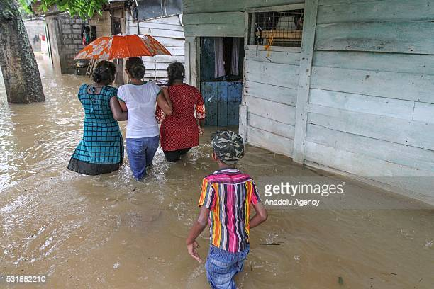 Sri Lankan people wade through floodwaters after heavy rain in Colombo Sri LankaTuesday May 172016