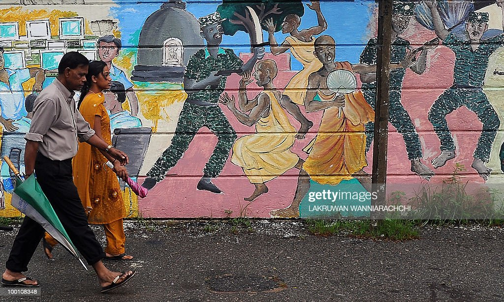 Sri Lankan people walk past a painting on a wall representing the kilings of Buddhist monks by the Tamil Tiger rebels in Colombo on May 21, 2010, a year after the defeat of the Tamil Tigers. A global human rights monitor said it had fresh evidence of possible war crimes committed in Sri Lanka during the final phase of the government's war against Tamil Tiger rebels. The New York-based Human Rights Watch (HRW) said it had examined over 200 photos taken on the front lines in early 2009 by a soldier from the Sri Lankan Air Mobile Brigade and had new witness accounts of troops shelling civilians. AFP PHOTO/Lakruwan WANNIARACHCHI
