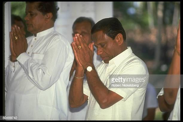 Sri Lankan P.M. Ranasinghe Premadasa, w. Head bowed & hands together, praying w. Unident. Others at Buddhist Temple.