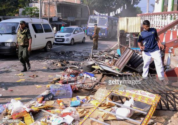 Sri Lankan police commandos patrol next to debris of from a damaged shop in the central district of Kandy on March 6 after a state of emergency was...