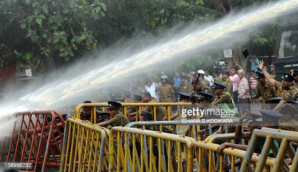Sri Lankan police crouch behind barricades as they unleash water cannon onto demonstrators in Colombo on February 15, 2012. Sri Lanka's Marxist JVP...