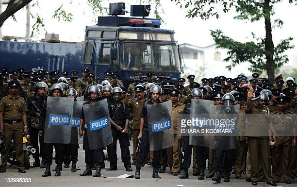 Sri Lankan police keep watch during a protest in Colombo on February 15, 2012. Sri Lanka's Marxist JVP party took to the streets against rising...