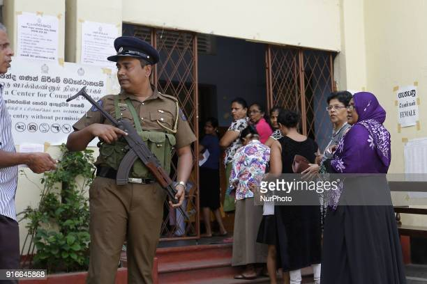 A Sri Lankan police officer stands next to Sri Lankan women voters lining up to cast votes at a polling station in Colombo Sri Lanka on Saturday 10...