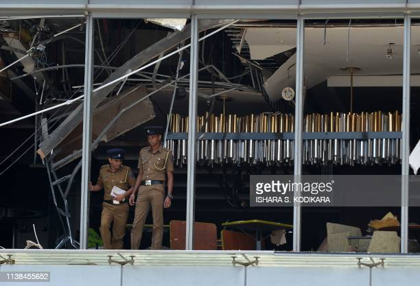 TOPSHOT Sri Lankan police stand at the site of an explosion in a restaurant area of the luxury ShangriLa Hotel in Colombo on April 21 2019 At least...