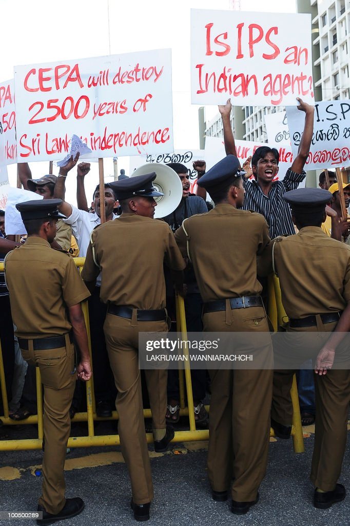 Sri Lankan police stand in front of a barricare holding back anti-Indian protesters on the main road leading to President Mahinda Rajapakse's official residence in the capital Colombo May 25, 2010. The demonstrators are opposing government plans to enter into a Comprehensive Economic Partnership Agreement with neighbouring India. AFP PHOTO /Lakruwan WANNIARACHCHI
