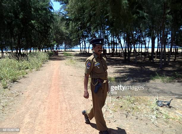A Sri Lankan policeman guards the site of a suspected mass grave in the eastern coastal town of Kalavanchikudy July 1 2014 A local magistrate put off...