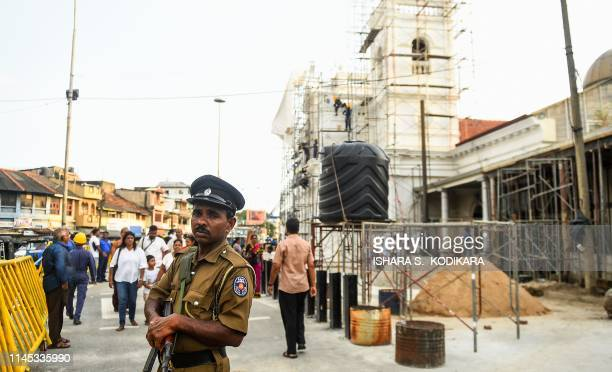 A Sri Lankan policeman stands guard as Catholic devotees take part in a remembrance ceremony in front of St Anthony's Church in Colombo on May 21 a...