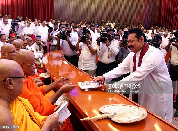 Sri Lankan President Mahinda Rajapaksa gives his party manifesto for Buddhist monks during the meeting to announce the party election manifesto on...
