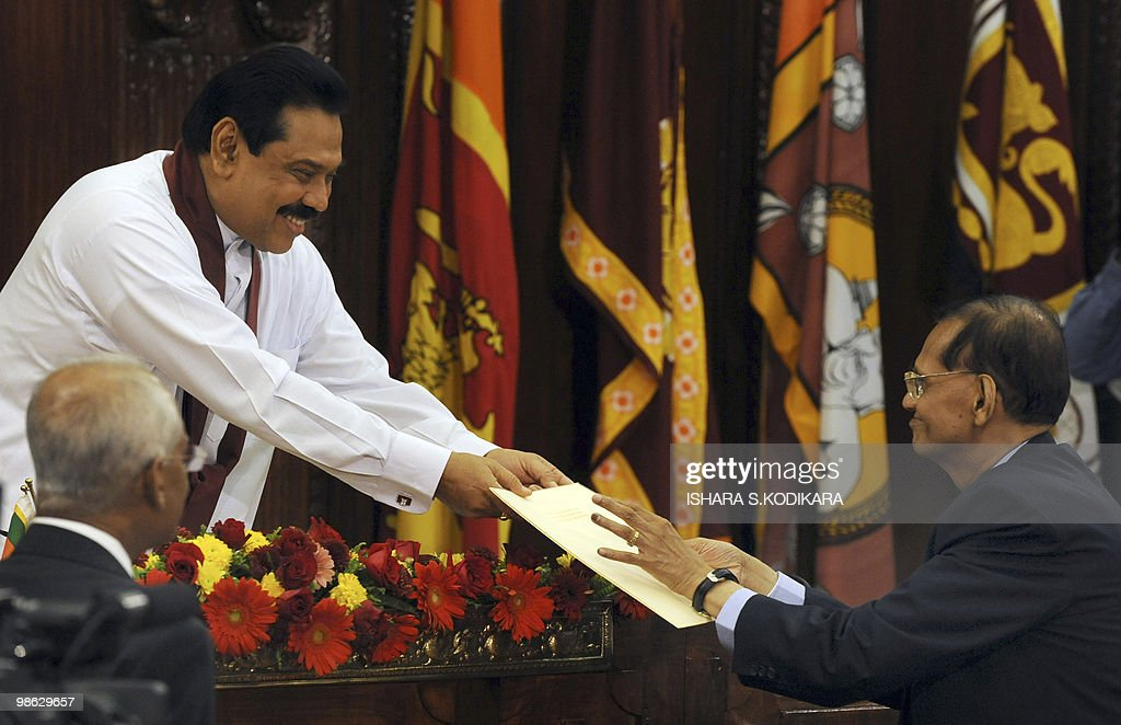 Sri Lankan President Mahinda Rajapaksa (L) hands over the letter of appointment to his new foreign minister Gamini Laxman Peiris in Colombo on April 23, 2010. Sri Lanka's new Cabinet was sworn in by Rajapakse folowing his parliamentary election win on April 8. AFP PHOTO/ Ishara S