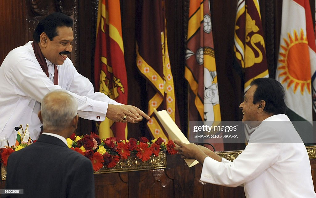 Sri Lankan President Mahinda Rajapaksa (L) hands over the letter of appointment to Prime Minister D.M. Jayaratne for his ministerial job of religious affairs in Colombo on April 23, 2010. Sri Lanka's new Cabinet was sworn in by Rajapakse folowing his parliamentary election win on April 8. AFP PHOTO/ Ishara S