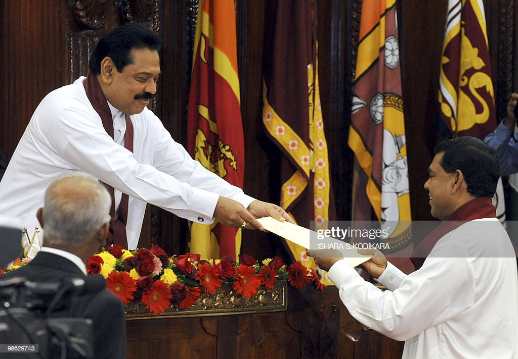 Sri Lankan President Mahinda Rajapaksa (L) hands over the letter of appointment to his younger brother Basil Rajapakse as the Minister of Economic Development in Colombo on April 23, 2010. Sri Lanka's new Cabinet was sworn in by Rajapakse folowing his parliamentary election win on April 8. AFP PHOTO/ Ishara S