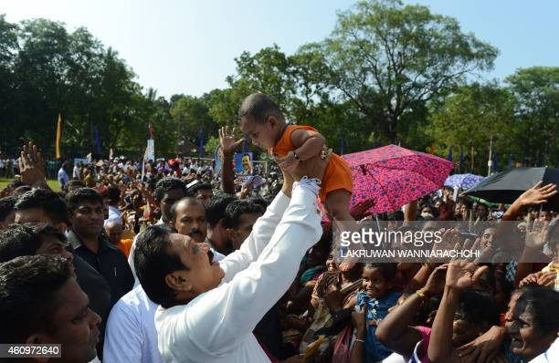 Sri Lankan President Mahinda Rajapaksa holds a baby as he interacts with supporters as a rally in the northern town of Vavuniya on January 2, 2015....