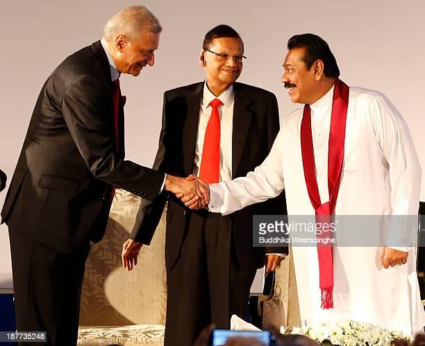Sri Lankan President Mahinda Rajapaksa shakes hands with Commonwealth Secretary-General Kamalesh Sharma as Sri Lankan Foreign Minister Gamini...