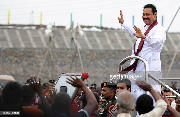 Sri Lankan President Mahinda Rajapaksa waves at supporters from the rear of an open vehicle during a inspection tour of a new port site at Hambantota...
