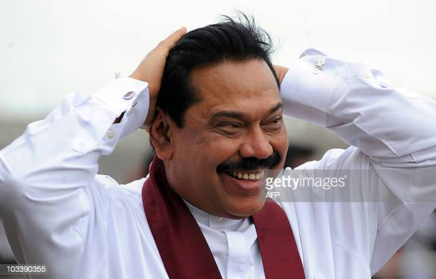 Sri Lankan President Mahinda Rajapakse gestures to supporters from the rear of an open vehicle during a inspection tour of a new port site at...