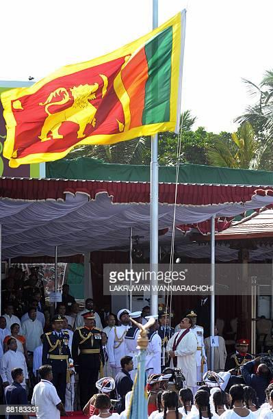 Sri Lankan president Mahinda Rajapakse hoists the national flag during the National Military Victory Celebration in Colombo on June 3 2009 Sri...